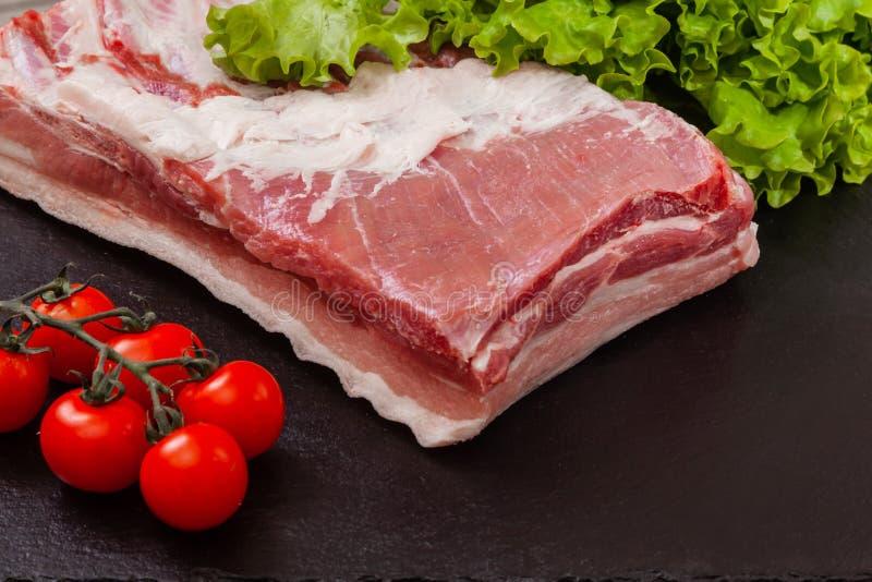 Часть мяса свинины на черной плите стоковая фотография