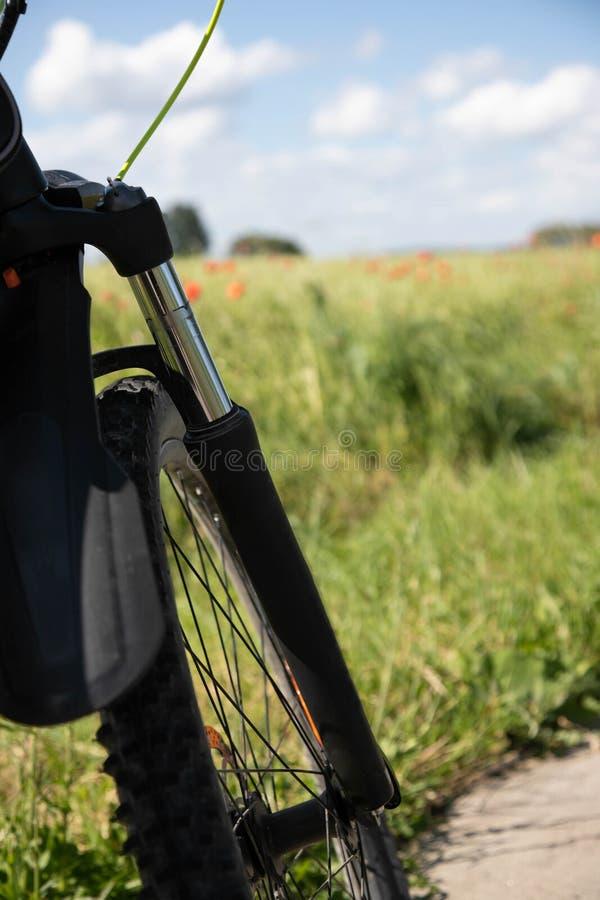Часть переднего колеса с resors на фоне поля рож зеленого цвета весны и красных маков стоковые фото