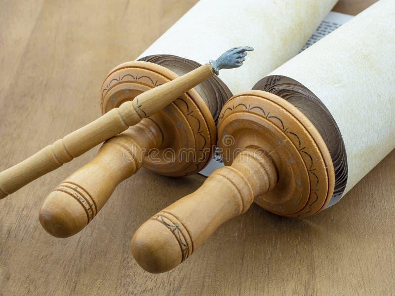 Часть переченей Torah с деревянным указателем на предпосылке деревянного стола коричневого цвета стоковое фото