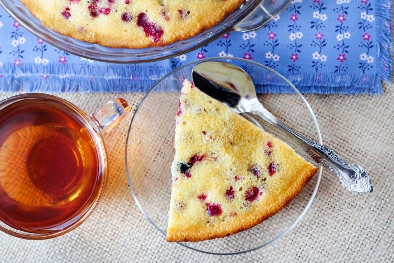Часть пирога cowberry на стеклянной пластинке и чашке чаю стоковые изображения