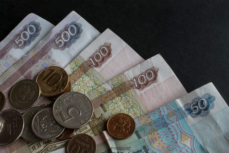 Часть русских бумажных денег и разбрасывать монет разного достоинства металла на их конец-вверх на черной предпосылке стоковое изображение