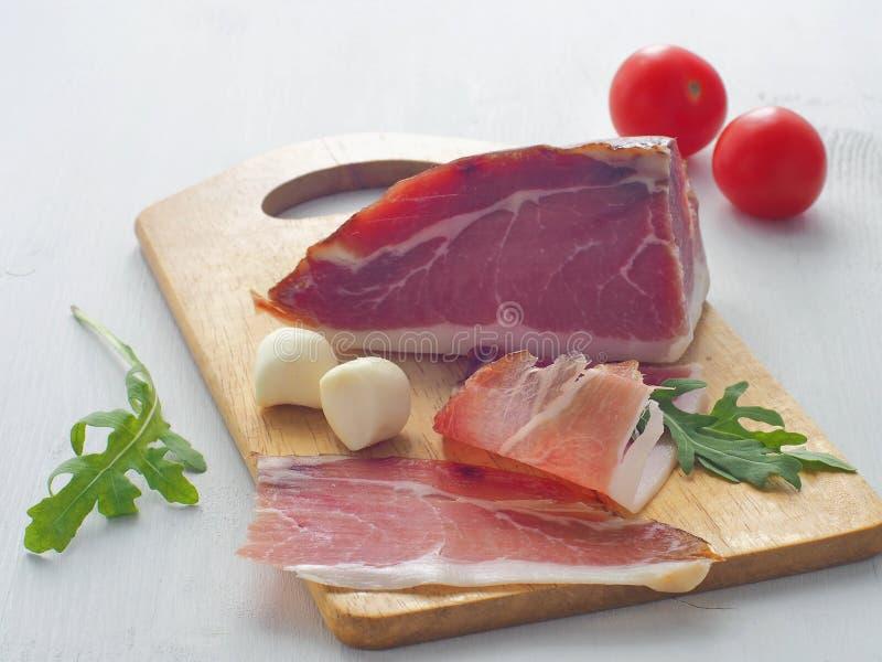 Часть свинины на белой таблице Ветчина, prsut, или испанское jamon с томатами вишни, свежим arugula и моццареллой стоковое фото