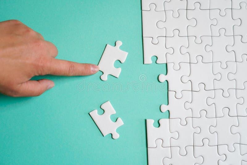 Часть сложенной белой мозаики и куча uncombed элементов головоломки на фоне покрашенной поверхности стоковые изображения
