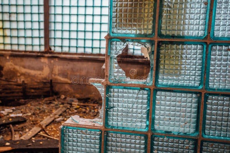 Часть сломленной стены от стеклянных блоков в покинутом промышленном здании стоковая фотография rf
