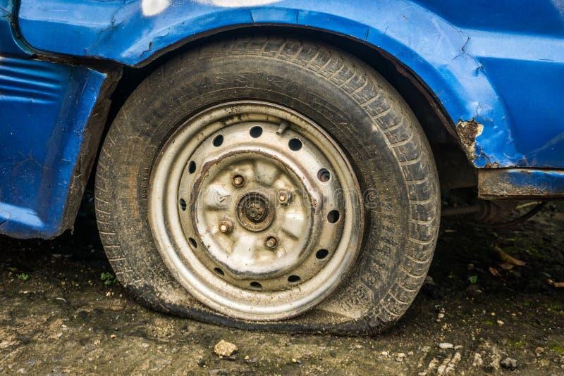 Часть спущенной шины покинутого голубого автомобиля припарковала в фото сада принятом в Depok Индонезию стоковые фотографии rf