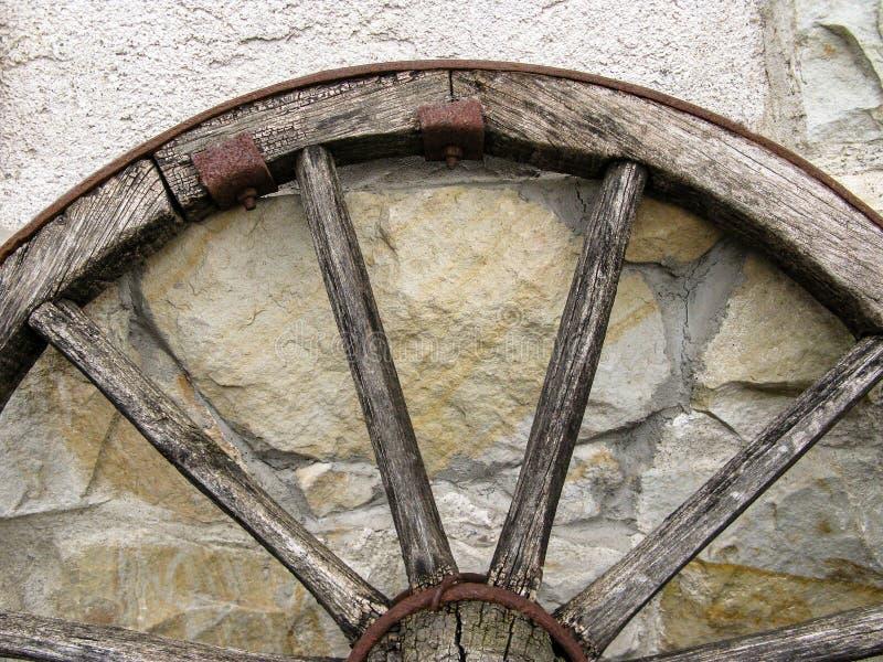 Часть старого деревянного колеса телеги против стены естественного камня стоковые изображения rf