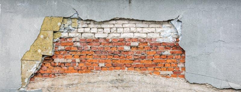 Часть старой разрушенной стены с поврежденными кирпичами, шерстями изоляции и грубой затрапезной штукатуркой стоковое фото rf