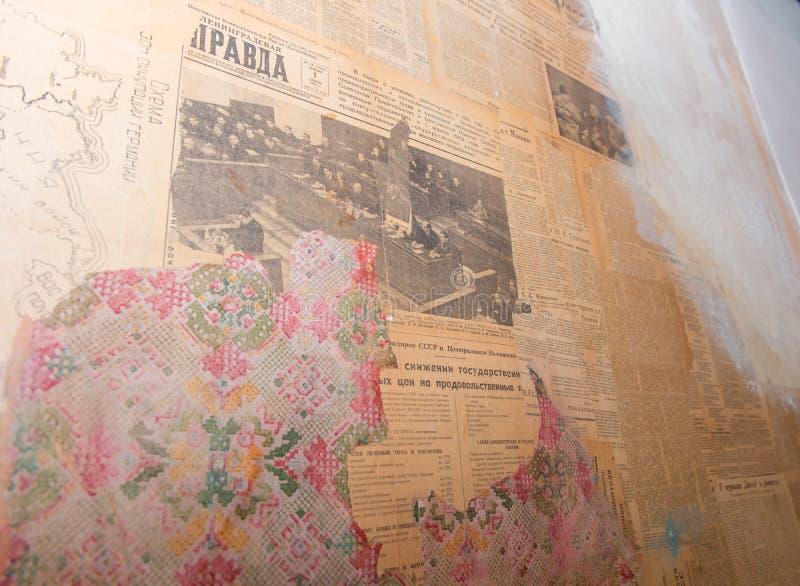 Часть старой стены с клочковатыми обоями и старыми коммунистическими газетами стоковое изображение rf