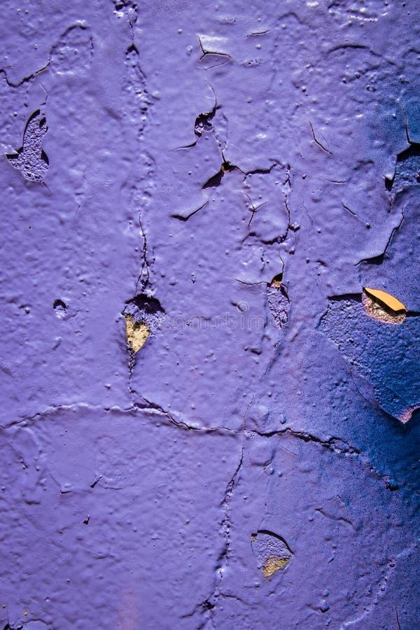 Часть старой стены с фиолетовыми, желтыми и фиолетовыми красками Шелушение фиолетовой краски Космос для текста стоковые фотографии rf