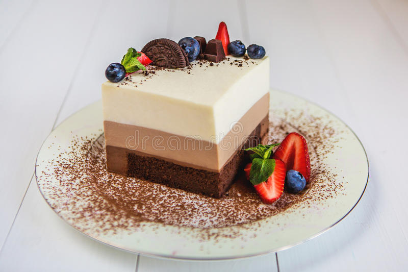 Часть стоек шоколада торта 3 мусса на плите, взбрызнутая с заскрежетанным шоколадом, и украшенная с ягодами стоковое изображение