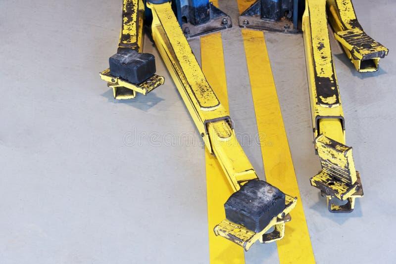 Часть столба lifter автомобиля в магазине автошины Концепция автомобильных и корабля Катите тему промышленного транспорта и запас стоковое фото