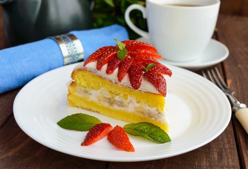 Часть торта губки банан-клубники украшая с листьями мяты на белых плите и чашке чаю стоковые изображения rf