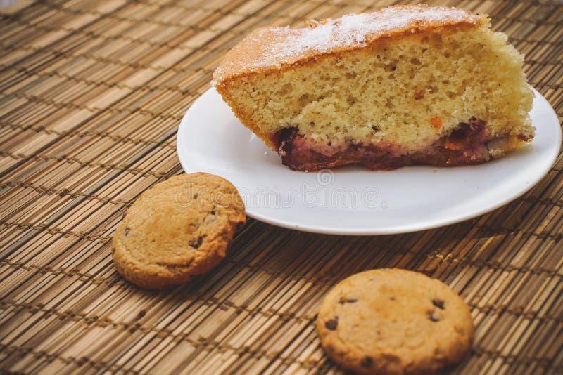 Часть торта губки на круглой белой плите с bis шоколада стоковое фото