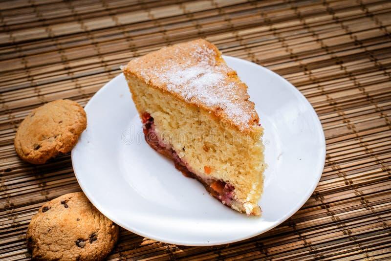 Часть торта губки на круглой белой плите с bis шоколада стоковое изображение rf