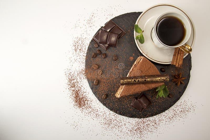 Часть торта тирамису на черном шифере стоковая фотография