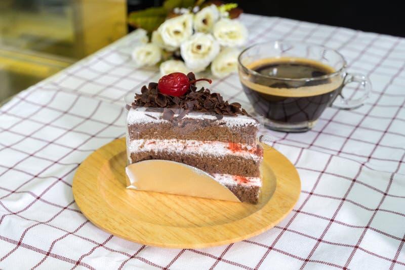 Часть торта черного леса на деревянных плите и кофейной чашке стоковая фотография