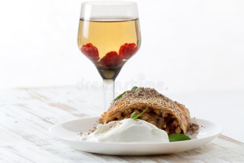 Часть традиционного пирога штрудели яблока служила с мороженым, свежей мятой, поленикой и бокалом вина стоковое фото rf