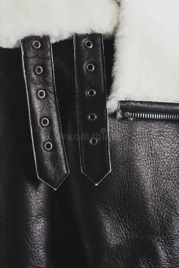 Часть черного кожаного пальто овчины с белым мехом стоковое изображение
