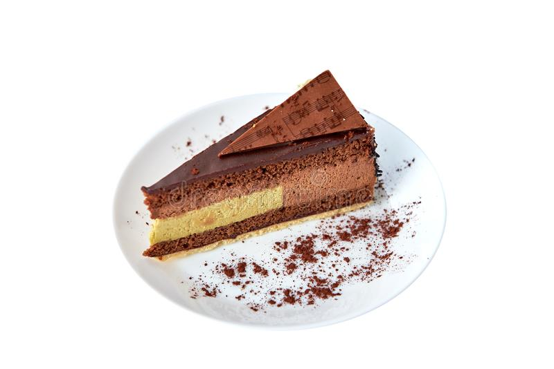 Часть шоколадного торта с фисташками и шоколадом на белизне изолировано Круглая плита с какао конец вверх стоковая фотография rf