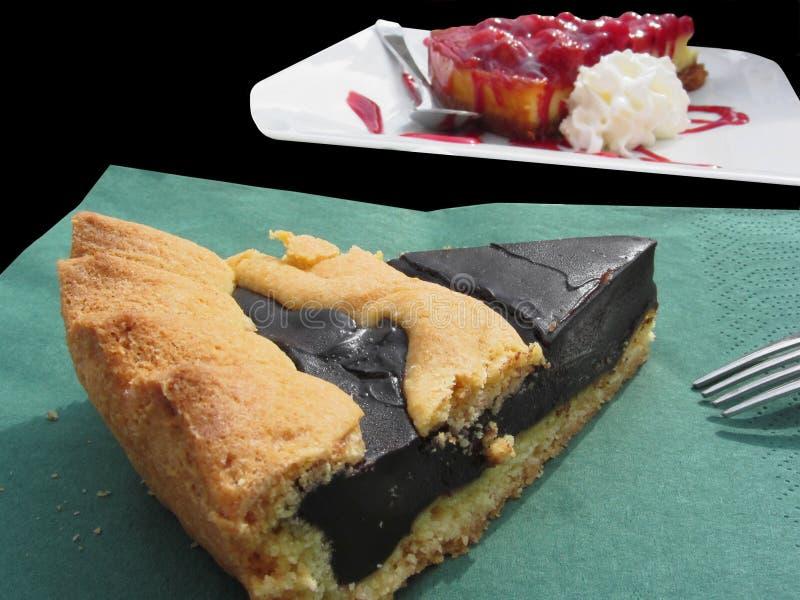 Часть шоколадного торта на салфетке зеленой книги и чизкейка мягких плодоовощей с свежими ягодами в предпосылке - на задней части стоковое фото rf