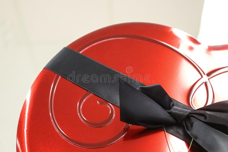 Часть элегантной красной коробки конфеты валентинки с черной лентой на светлой предпосылке стоковые изображения rf