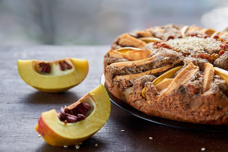 Часть яблочного пирога с айвой, маковыми семененами, изюминками и сезамом на темной плите украшенной с отрезанной свежей айвой стоковые изображения