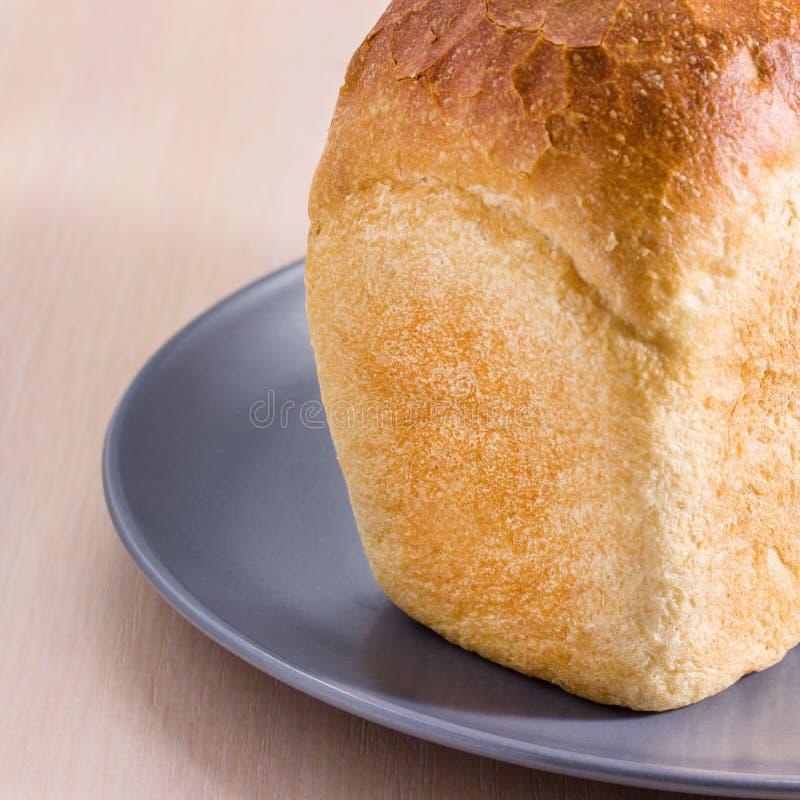 Часть яркого хлебца белого хлеба на голубой плите стоковое изображение