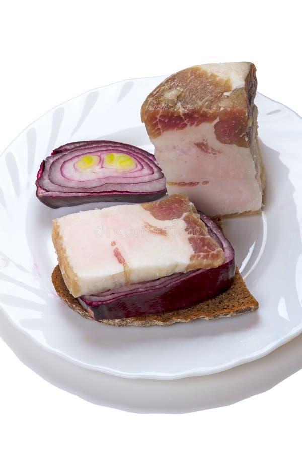 Часть brackish бекона на хлебе рож и красном луке стоковая фотография