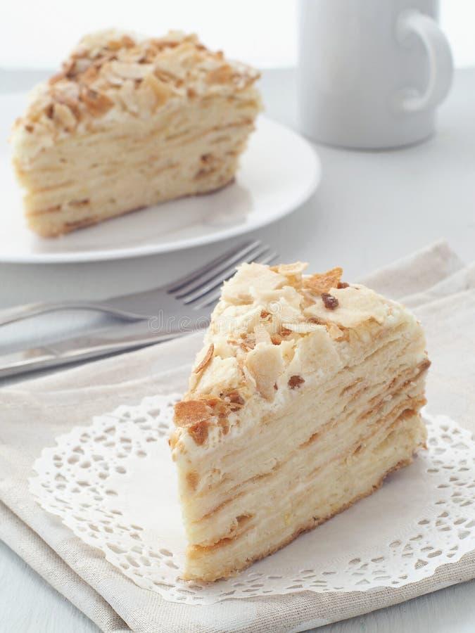 Часть multi конца-вверх наслоенного торта Десерт feuille Mille Мякиши украсили torte на белом doily на деревянном столе стоковые изображения