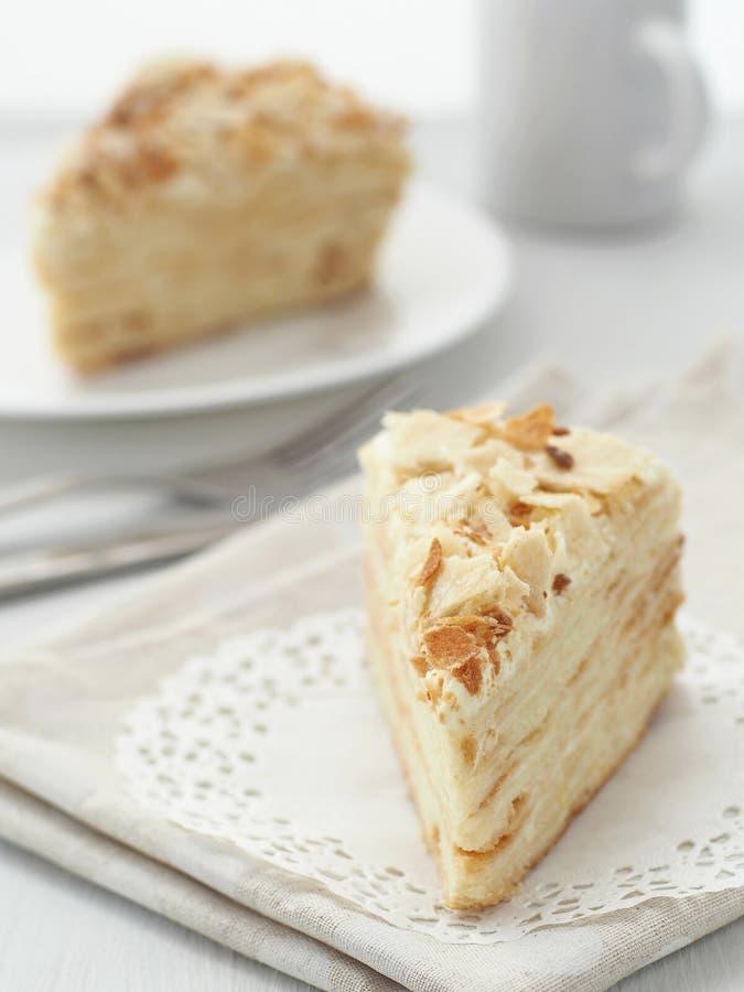 Часть multi конца-вверх наслоенного торта Десерт feuille Mille Мякиши украсили torte на белом doily на деревянном столе стоковые изображения rf