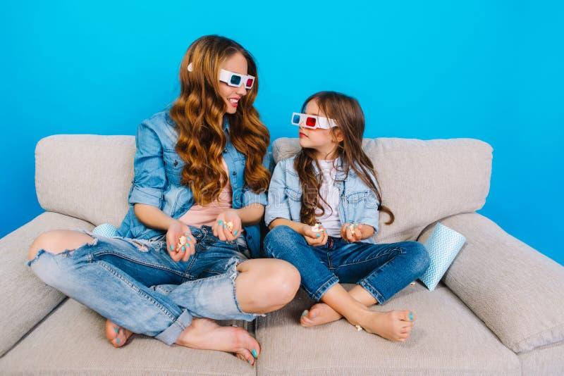 Часы досуга совместно изумлять красивую мать с ее молодой дочерью на кресле на голубой предпосылке Наблюдать стоковая фотография rf
