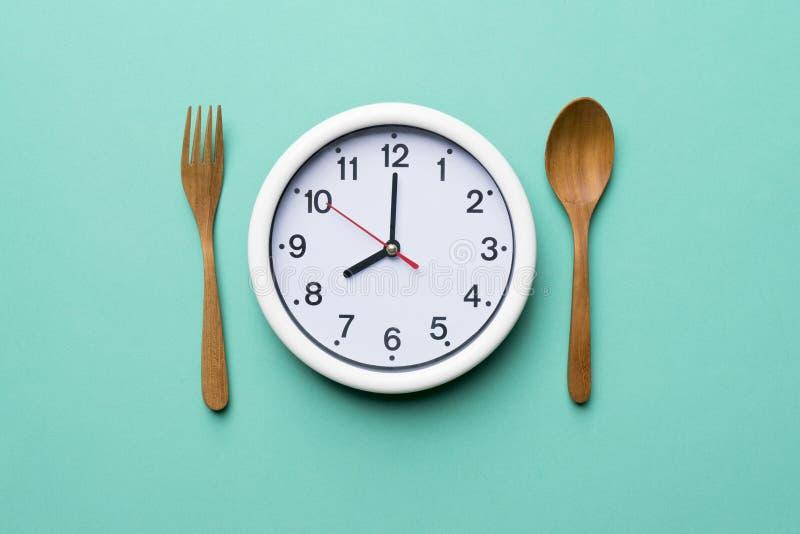 Часы еды с деревянными ложкой и вилкой стоковые изображения rf