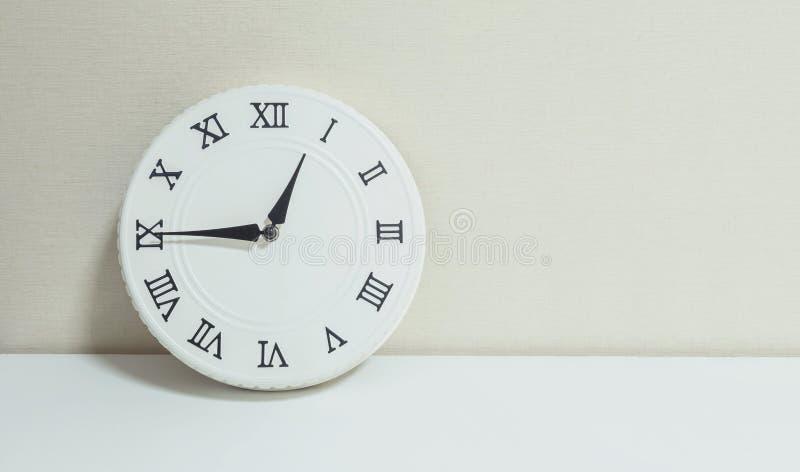 Часы крупного плана белые для украшают выставку квартал до один p M или 12:45 p M на белых деревянных столе и сливк обои текстури стоковая фотография
