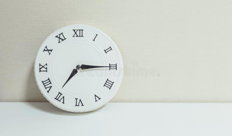 Часы крупного плана белые для украшают выставку квартал за 7 или 7:15 a M на белых деревянных столе и сливк обои текстурировали п стоковые изображения rf
