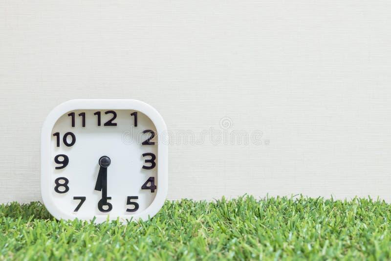 Часы крупного плана белые для украшают выставку половина за 6 или 6:30 a M на зеленой искусственной траве обои пола и сливк текст стоковые изображения rf