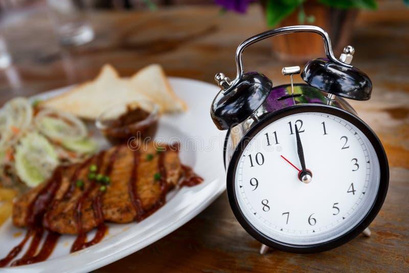 Часы на деревянном столе с стейком на предпосылке стоковые фото