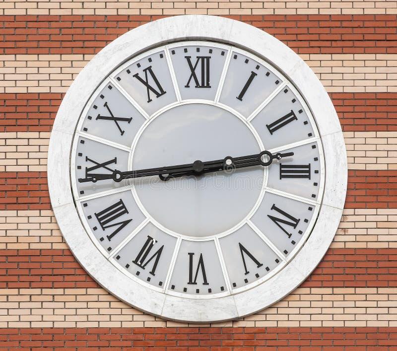 Часы на предпосылке кирпичной стены стоковое изображение