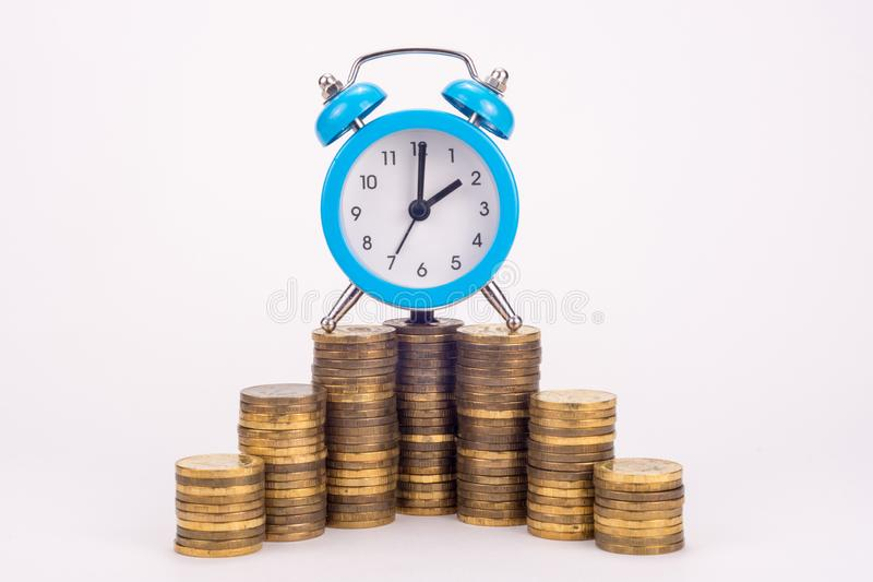 Часы на стоге монеток стоковое фото