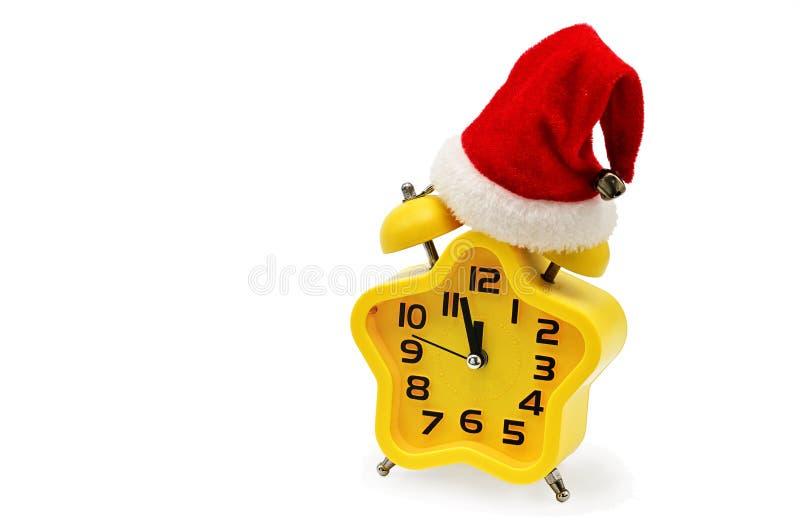 Часы рождества звездочки показывают остальное время до полуночи со шляпой Санта Клауса, на белой предпосылке yellow 12, 12 стоковая фотография rf