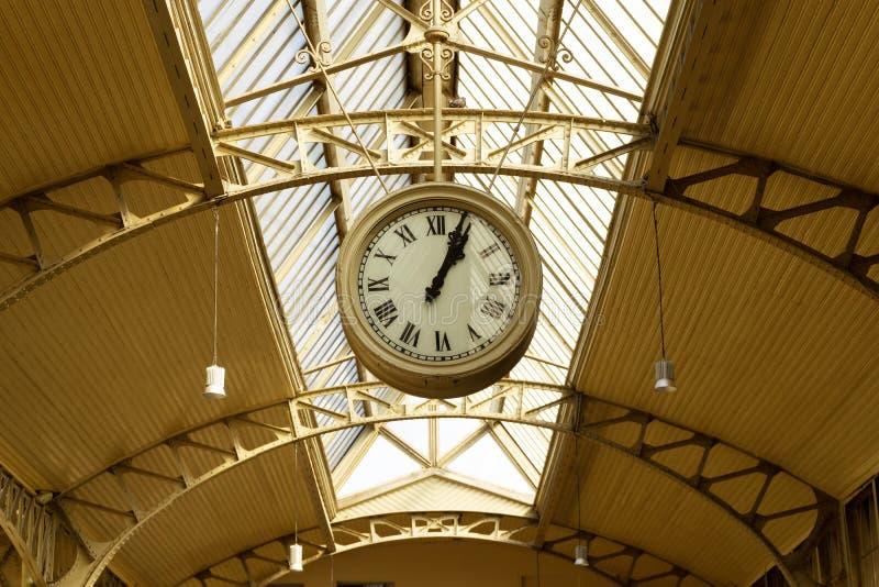 Часы станции висят на потолке старой станции стоковое фото
