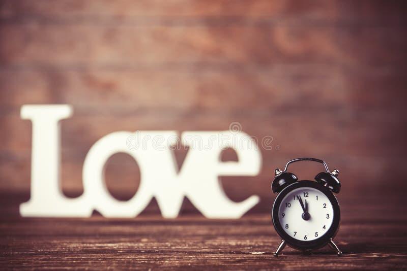 Часы с влюбленностью слова стоковая фотография