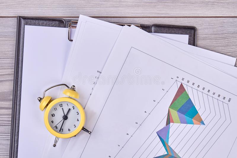 Часы тревоги и обработка документов офиса стоковое изображение