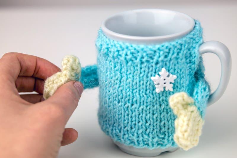 Чашка в связанном свитере с руками стоковое изображение rf