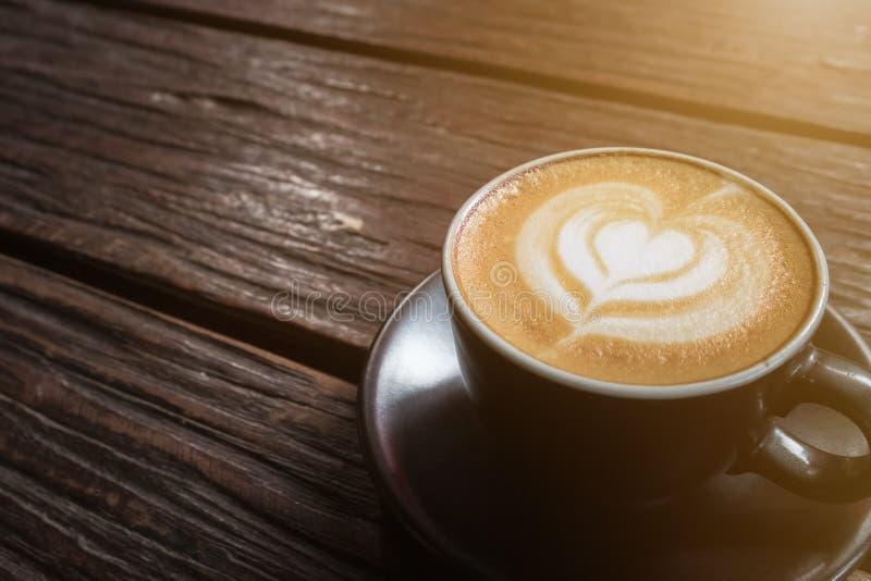 Чашка горячего кофе искусства latte на деревянном столе стоковое изображение