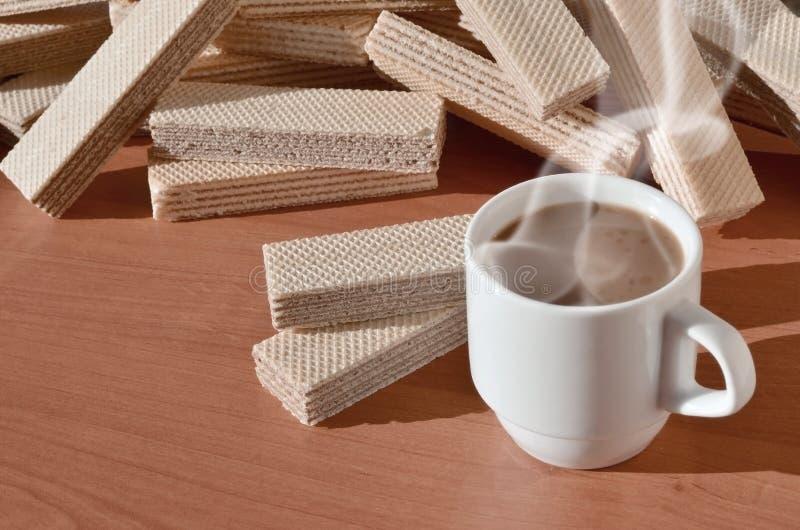 Чашка горячего кофе и пригорошня классических русских waffles с различными завалками на коричневой деревянной поверхности Натюрмо стоковое фото