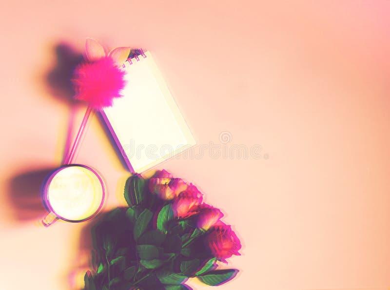 Чашка горячего кофе, пустого блокнота со смешной ручкой и букета свежих роз на мягкой розовой предпосылке Изображение влияния неб стоковое изображение rf