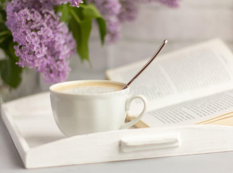 Чашка горячего кофе с молоком, букет сиреней и открытая книга на таблице, времени остатков стоковое фото rf