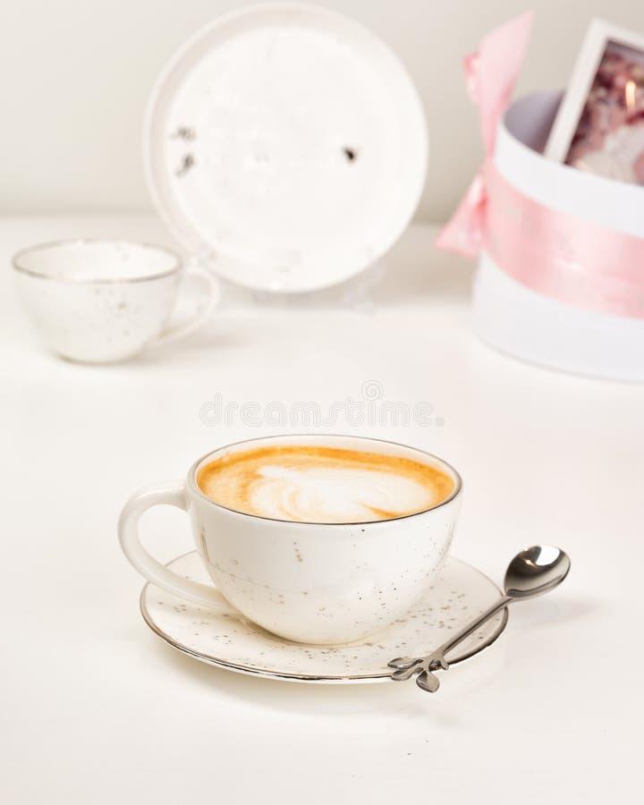 Чашка горячего кофе Latte искусства на белой таблице в кофейне стоковое изображение rf