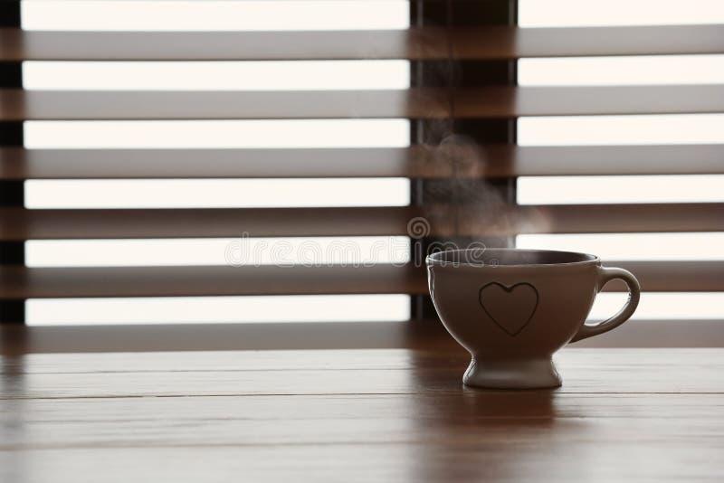 Чашка горячего чая на деревянном столе около окна со шторками стоковые фото