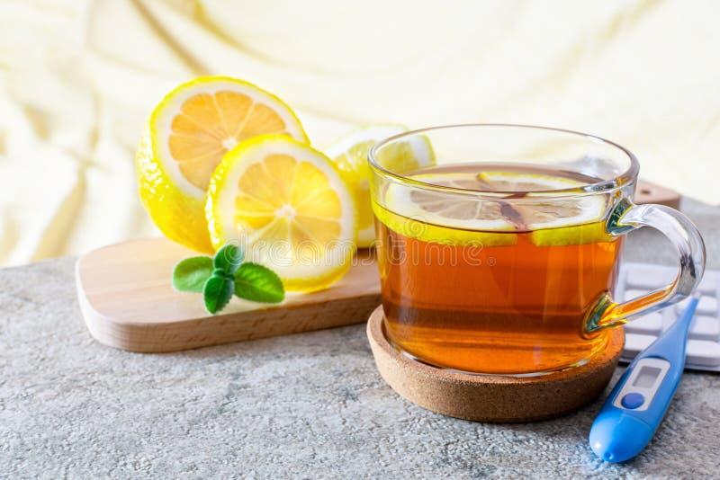 Чашка горячего чая с лимоном и мятой для лечения болезни на деревянной доске, термометре и таблетки для холодного гриппа стоковое фото rf